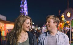 A couple asking each other dating questions while on a first date at a fair.