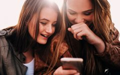 Two girls who are looking for a dating app like Tinder laughing at their phone using a Tinder alternative app.