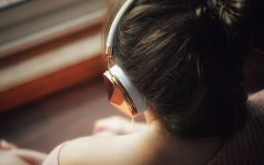 A woman listening to songs about missing someone and I miss you songs on a train.
