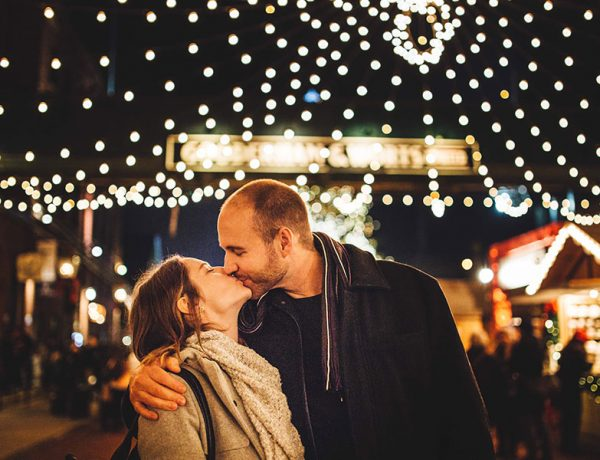 A couple of over 40 singles kissing under some holiday lights.