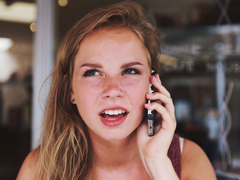 A girl on the phone who is confused about outdated dating rules like the three day rule.