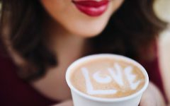 A woman who's single in her 40s sipping from a coffee cup that says love in it.