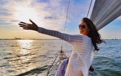 A woman who got help on how to move on, celebrating and looking happy on a boat during a sunny day.