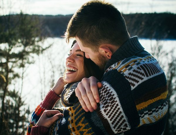 A woman hugging her boyfriend and trying not to misread the dating signs.