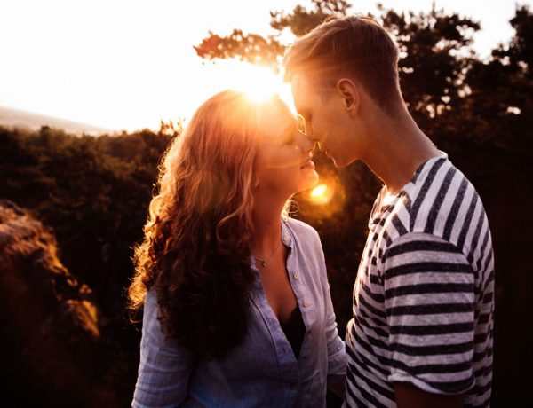 This woman figured out the six things guys do when they like you and is happy kissing her boyfriend in the sun.