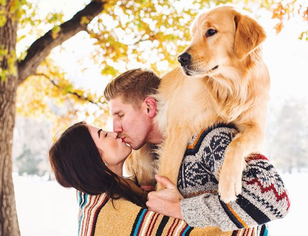 A couple kissing with their dog on the man's back.