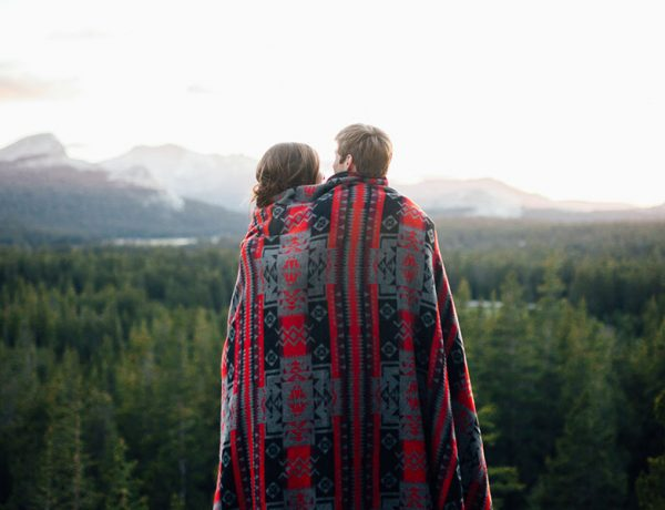 A couple who took these dating tips for frequent travelers and are now looking at a mountain and hugging.