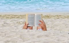 A woman being single and happy as she reads a book on the beach.