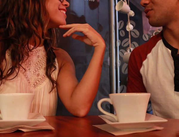 A couple who took these first date conversation tips chatting over coffee and laughing.