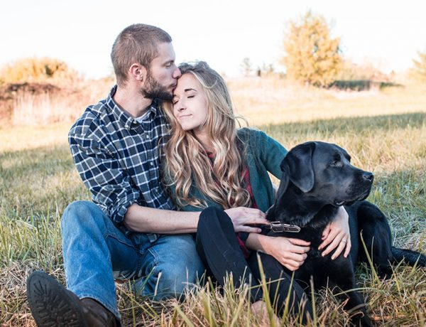 A couple rural dating in a small town kissing in a field with their dog.