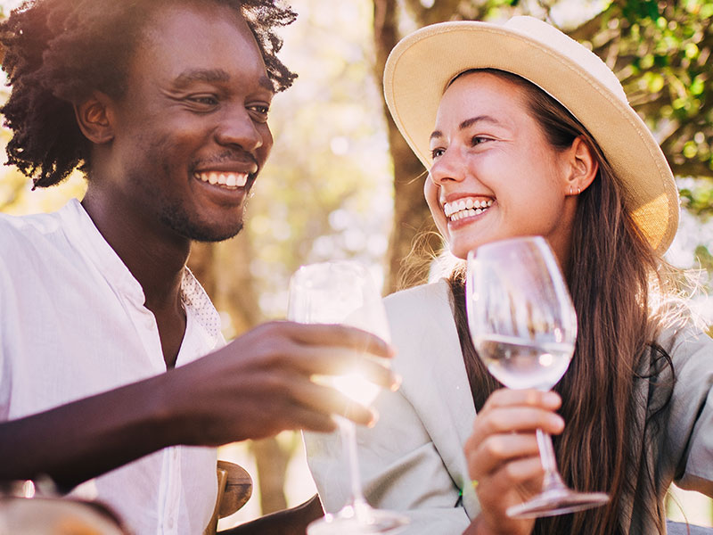 A couple laughing at an outdoor restaurant after taking these dating tips from a chef.