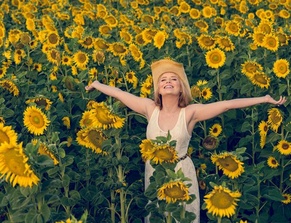 A women being single and happy in a field of sunflowers.