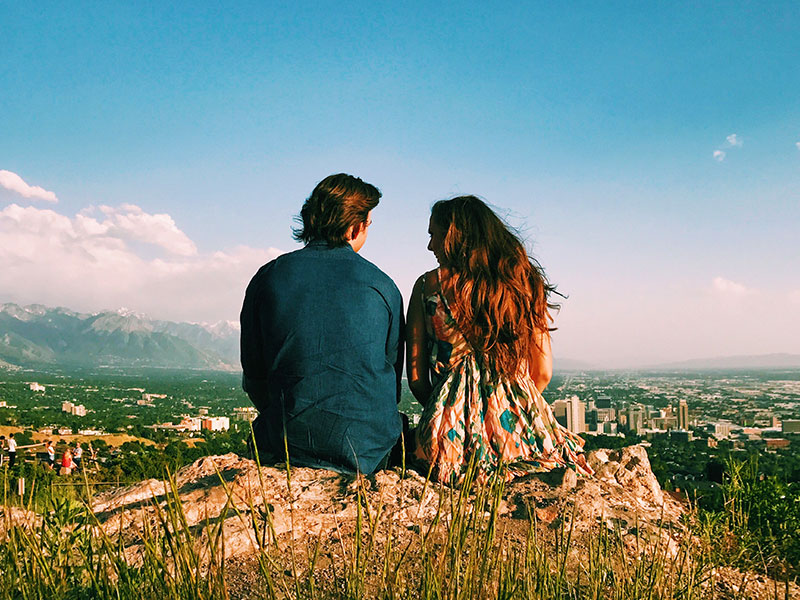 A couple sitting on top of a mountain who listened to these first date conversation tips having a great first date.