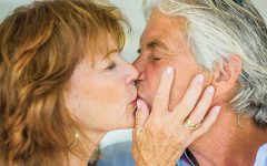 A 60 year old men in a relationship kissing a woman he's happy with.