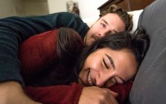 A happy couple who just finishing moving in together giggling in bed.