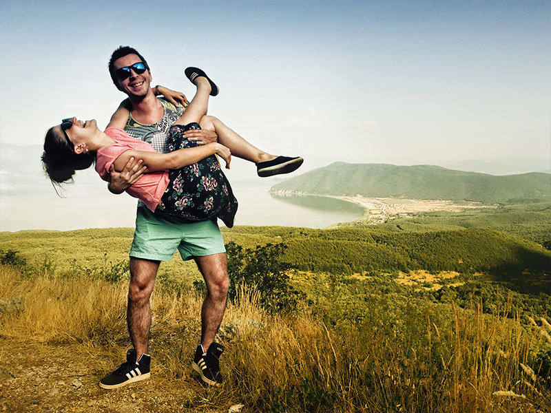 A couple laughing on a hike because they learned how to strengthen your relationship.
