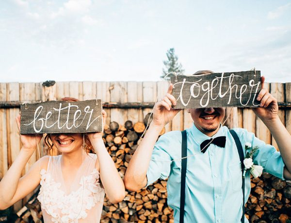 A couple holding up signs at their wedding that say better together.
