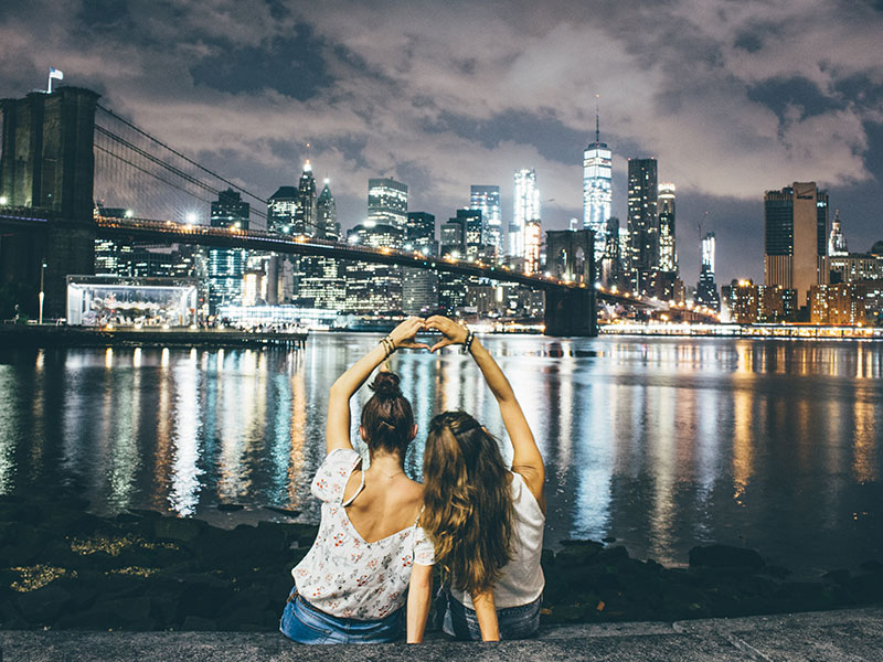 Two millennial girls sitting in front of a city scape on a dating, making a heart sign.