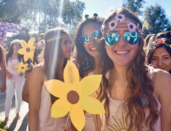 Get some dating tips from a former sorority girl like this one holding a yellow flower at bid day.