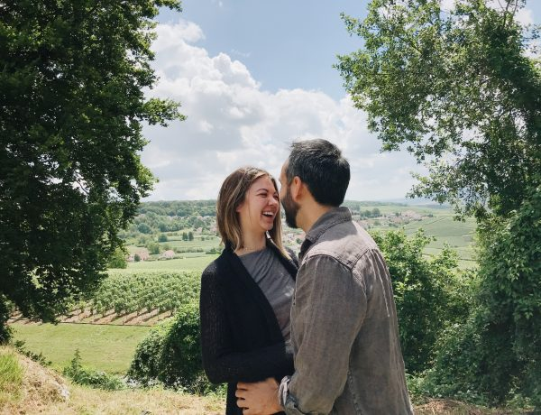 A woman who's dating again at 40 laughing with a man on a hill while wine tasting.