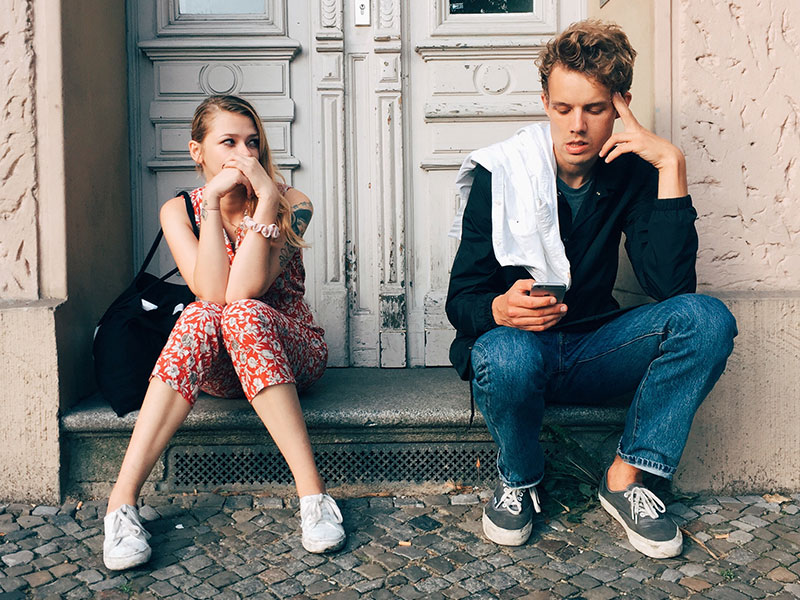 A girl annoyed with her boyfriend while he talks on his phone, thinking these could be signs it's time to break up.