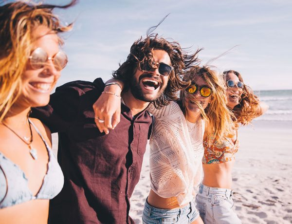 A group of highly successful singles laughing on a beach while they live the single life feeling confident in themselves.