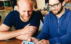 Two men reading a dating message together on one of their phones.
