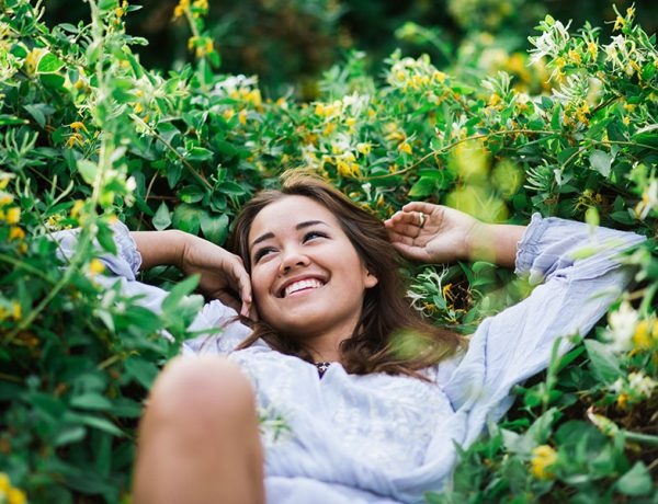 A woman who got over being unlucky in love, laughing in a pile of flowers and grass because now she's happy.