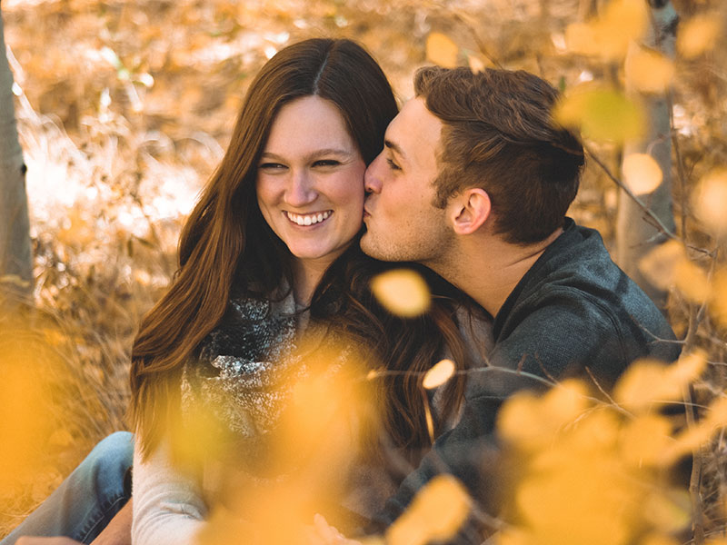 A woman who paid attention to these signs that he likes you and is now laughing in the fall leaves while the guy she likes kisses her cheek.