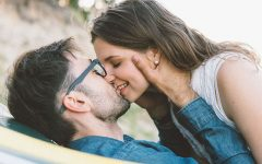A woman who figured out dating meaning kissing her boyfriend and smiling.