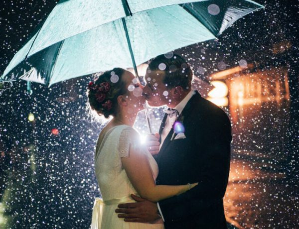 A couple answering the question, what is romance? by kissing in the rain.