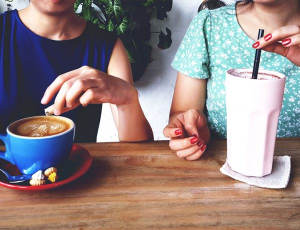 Two people who met while online dating in recovery drinking coffee and a milkshake on a date.