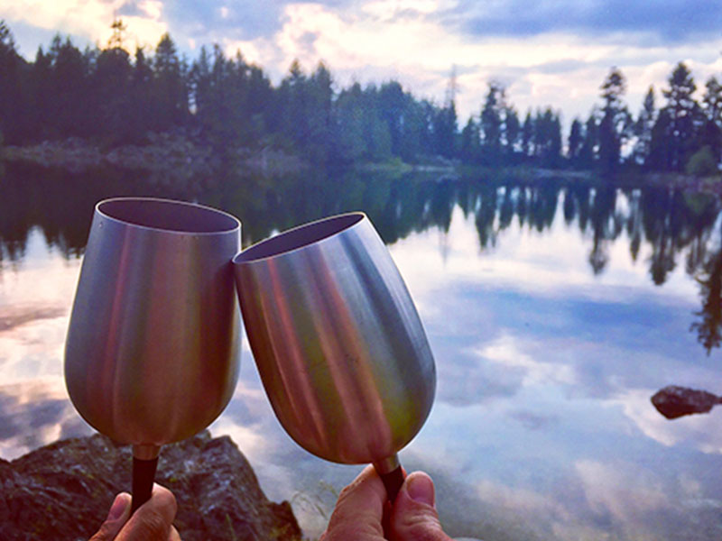 Two people making their first date more fun by having some wine by a lake.