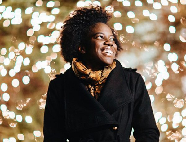 A woman who's single during the holidays smiling while looking at a Christmas tree in the city.