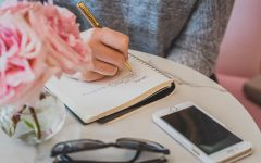 A professional matchmaker writing in her notebook while planning a date for someone.