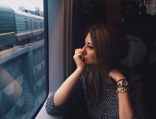 A woman who likes being single sitting on the train, smiling as she looks out the window.