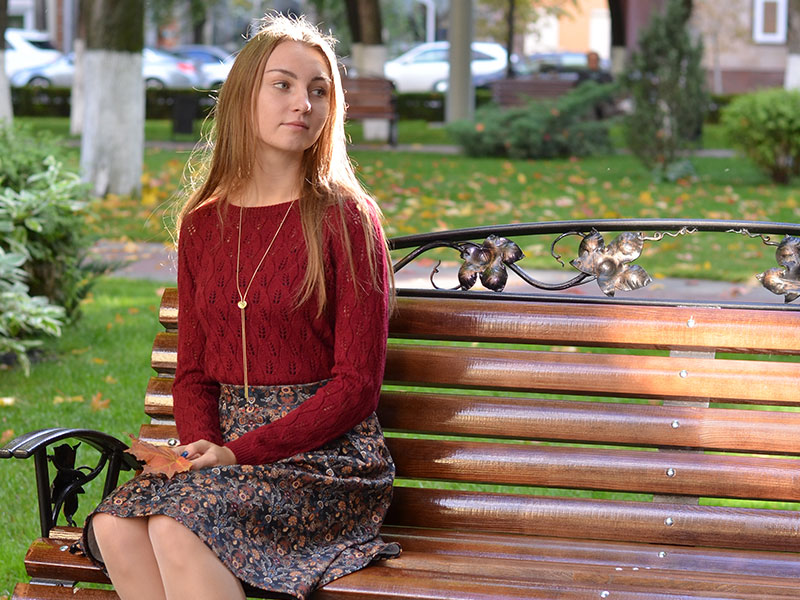 A woman who's still single, sitting on a park bench alone.