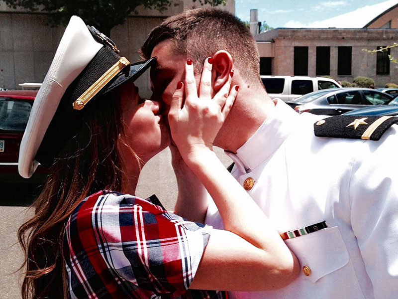 A woman kissing her boyfriend who's in the military because of their military love stories.