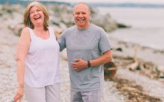 A cute couple dating over 50, laughing and holding hands on the beach.