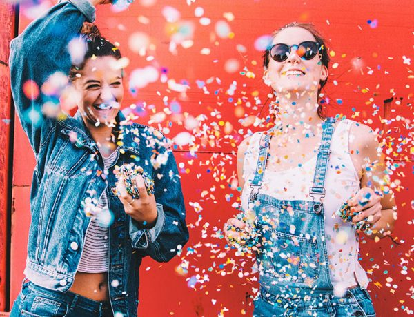 Two young girls throwing confetti being happy.