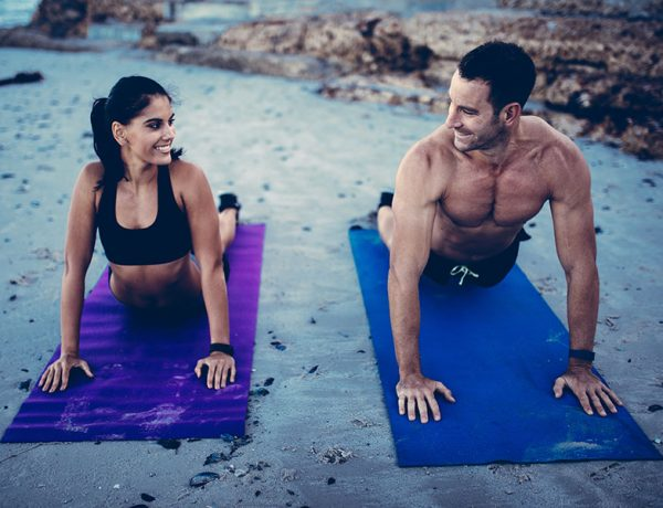 A happy couple doing yoga together on the beach and smiling at each other.
