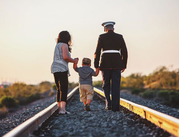 A couple in the U.S. military walking down some rail road tracks with their son.