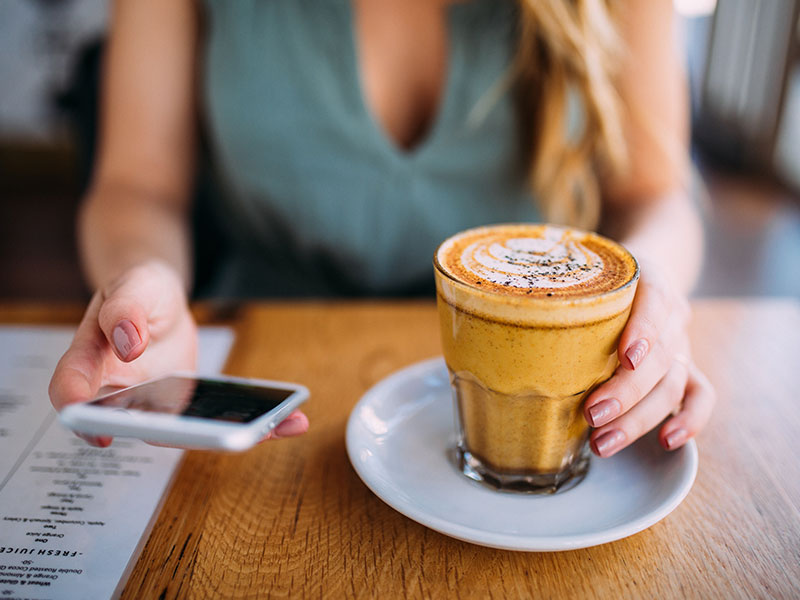 A woman who took these online dating tips for women to write a good message on her phone while drinking coffee.