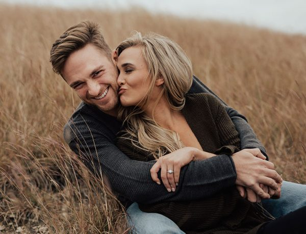 This couple kissing and laughing in a field listened to these relationship tips from happy couples.