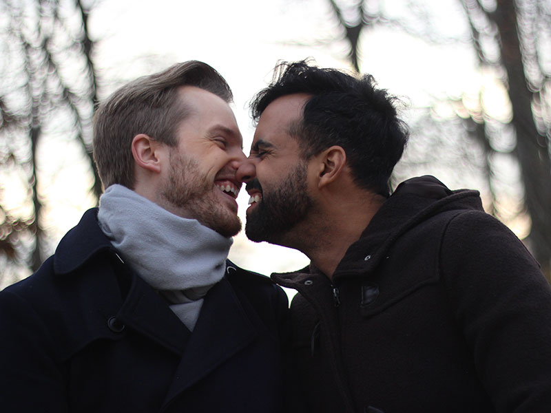 A gay couple touching noses and laughing after they met by going on fewer, but better, dates.