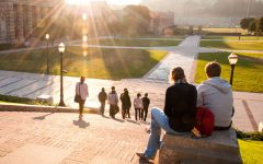 A couple dating in college sitting on a rock by the library watching the sun set on campus.