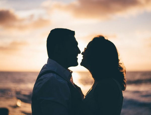Two people who are senior dating looking into each other's eyes at sunset on a beach.