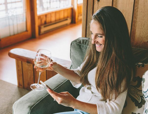 A woman who was wondering how to talk to guys online typing on her phone while drinking wine.