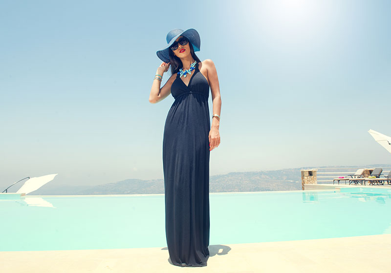 A woman who took these date outfit ideas wearing a black maxi dress in front of a pool.