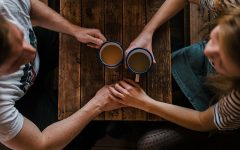 Two singles over 40 holding hands while on a date at a coffee shop.
